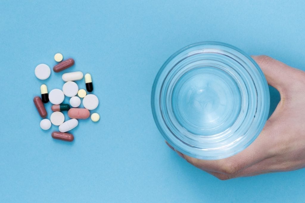 top view pills with hand holding glass water